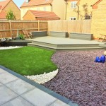 Composite decked area, granite paving, purple slate & artificial turf.